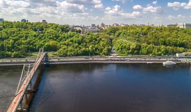 Vista aérea do zangão da ponte pedonal do parque, do rio dnieper e da paisagem urbana de kiev de cima, cidade de kiev, ucrânia