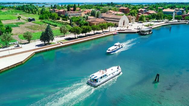 Vista aérea do zangão de casa flutuante na lagoa veneziana, cruzeiro de viagens em família de barco de férias na itália