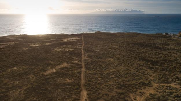 Vista aérea do zangão do oceano atlântico ao pôr do sol, terreno de arbustos e caminhos. no horizonte a passagem de um navio