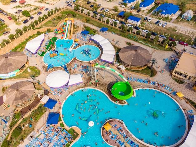 Vista aérea do zangão, olhando diretamente para baixo acima de diversão de horário de verão colorido no parque aquático