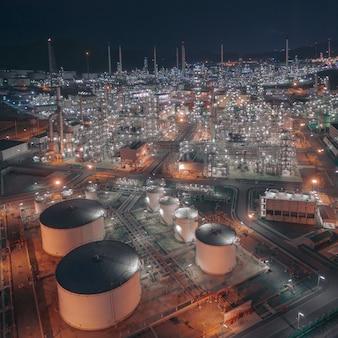 Vista aérea do zangão sobre enorme fábrica de refinaria de petróleo à noite com muitos tanque de armazenamento e oleoduto da torre de destilação.