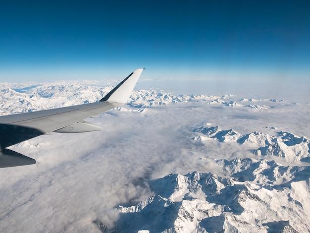 Vista aérea dos alpes suíços italianos no inverno, com a asa genérica do avião. cordilheira coberta de neve e glaciares. visão expansiva, céu azul claro.