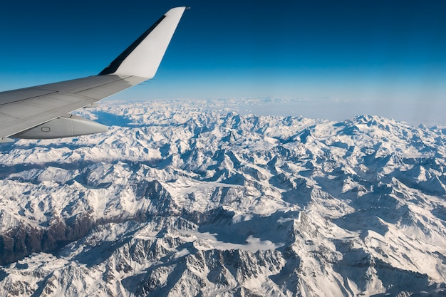 Vista aérea dos alpes suíços italianos no inverno, com asa de avião genérico.