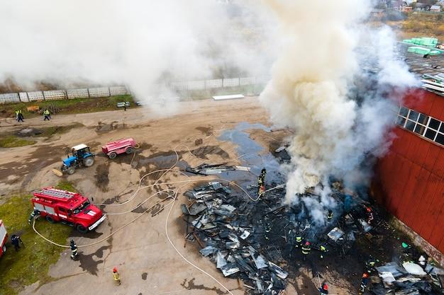 Vista aérea dos bombeiros apagando incêndio em área industrial.