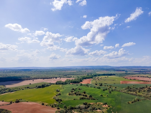 Vista aérea dos campos de castela com parcelas agrícolas e céu azul com nuvens