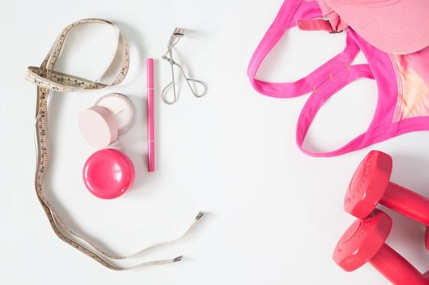 Vista aérea dos itens de beleza essenciais, halteres vermelhos, sutiã esportivo e cosméticos, vista superior isolada no fundo branco