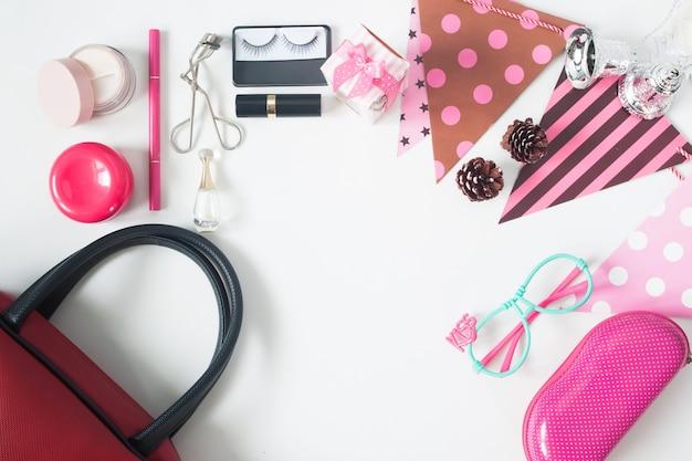 Vista aérea dos itens de beleza essenciais, vista superior dos acessórios do partido, saco de mão vermelho, óculos de moda e cosméticos, vista superior isolada no fundo branco