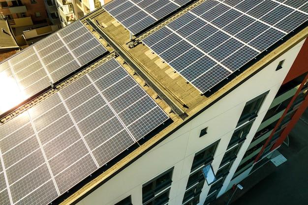 Vista aérea dos painéis solares fotovoltaicos em uma parte superior do telhado do bloco de construção residencial para a produção de energia elétrica limpa. conceito de habitação autônoma.