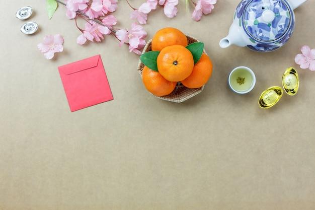 Vista aérea dos principais itens essenciais feliz ano novo chinês. outra linguagem significa riqueza ou riqueza e felicidade. misture vários objetos no escritório de escritório de madeira cinza moderno. espaço livre para projetos.