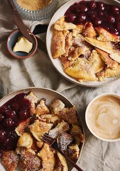 Vista aérea em close up de deliciosas panquecas fofas com cereja e açúcar de confeiteiro