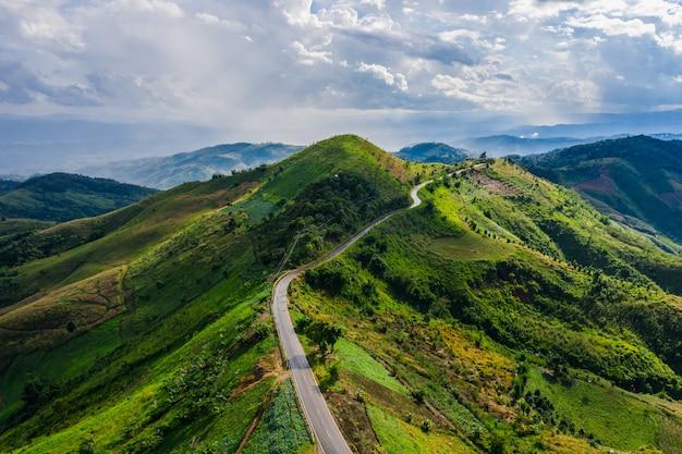 Vista aérea estrada caminho no pico da montanha verde na estação de chuva e manhã névoa e céu azul