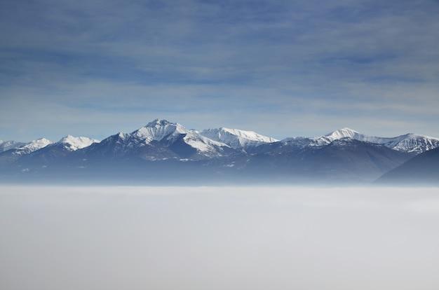 Vista aérea incrível de montanhas parcialmente cobertas de neve e posicionadas acima das nuvens