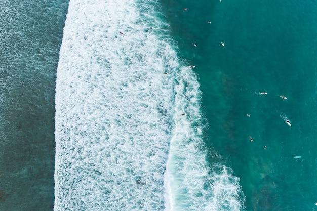 Vista aérea incrível top down das ondas quebram no mar tropical surfistas com pranchas de surf vista aérea do drone das ondas do mar no belo oceano em phuket, tailândia.