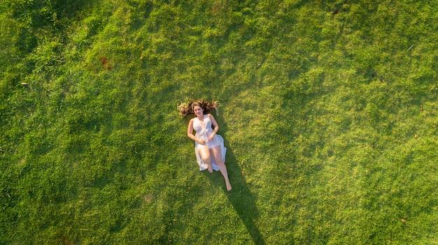 Vista aérea. moça que encontra-se e que descansa no gramado no dia ensolarado no parque na grama.