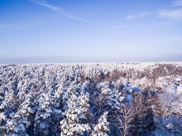 Vista aérea na neve inverno floresta e vila céu azul no fundo os telhados estão sob a neve