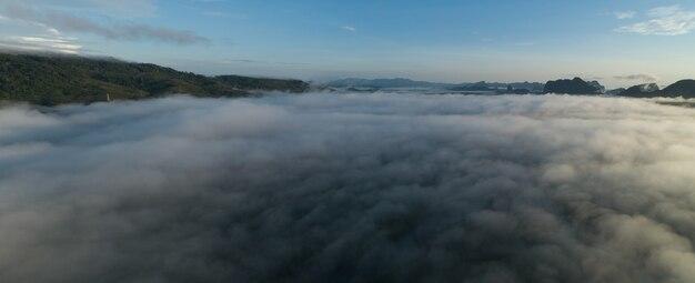 Vista aérea panorama das ondas de nevoeiro fluindo na floresta tropical da montanhaimagem da vista do pássaro sobre o