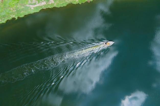 Vista aérea panorâmica de barco branco flutuando em águas cristalinas azul-turquesa Foto Premium