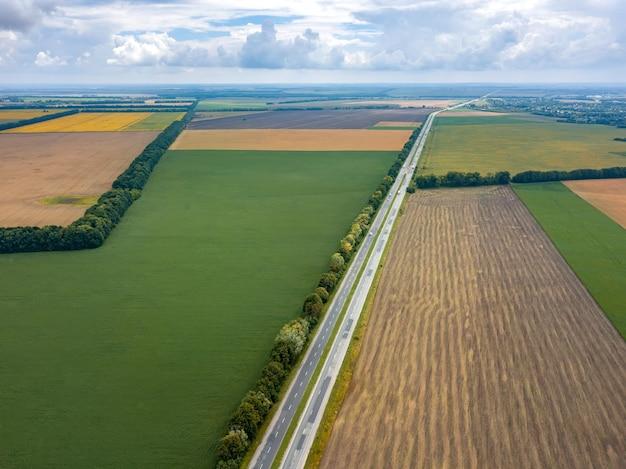 Vista aérea panorâmica de uma rodovia com carros, campos, plantação de árvores ao pôr do sol de verão. vista superior do drone voador.
