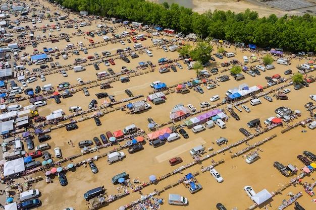 Vista aérea panorâmica do mercado de pulgas com diversos itens e multidões de compradores e vendedores