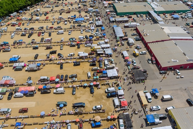 Vista aérea panorâmica do mercado de pulgas com diversos itens e multidões de compradores