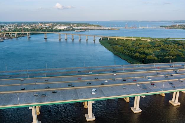Vista aérea panorâmica do tráfego rodoviário de carros dirigindo na rodovia do outro lado da ponte