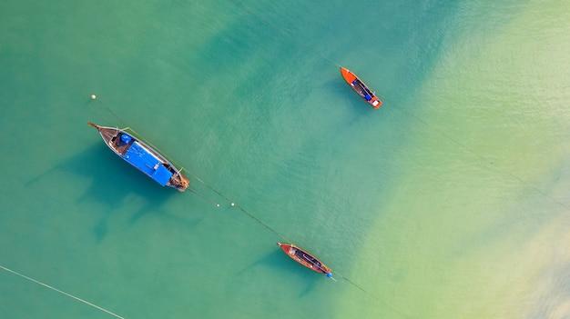 Vista aérea superior, barco de pesca, barco turístico flutuando em um mar claro raso