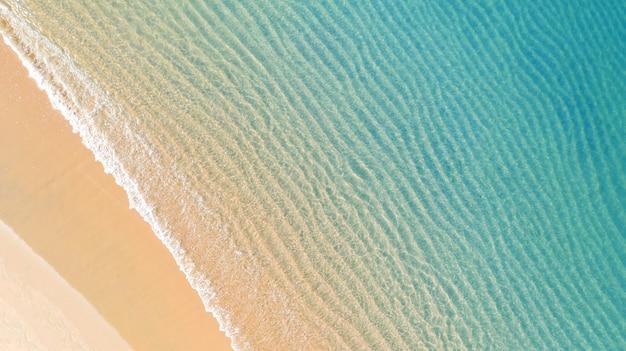 Vista aérea superior da praia com sombra água azul esmeralda e espuma de onda no mar tropical