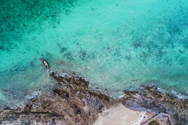 Vista aérea superior das ondas do mar, praia e litoral rochoso e bela floresta.
