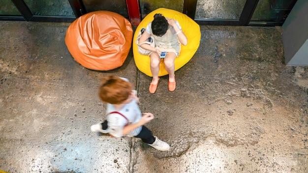 Vista aérea superior de mulher caminha com pufe amarelo no chão.