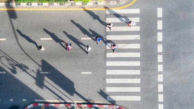 Vista aérea superior de pessoas do grupo a pé na cidade de rua com faixa de pedestres na estrada de tráfego de transporte.