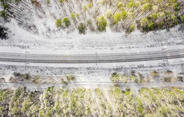 Vista aérea superior de uma ferrovia de mão dupla na floresta no dia ensolarado de inverno. conceito de transporte.