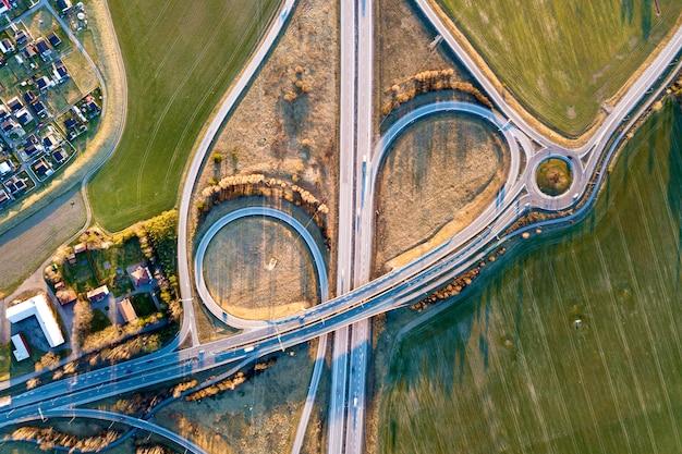 Vista aérea superior do cruzamento de estrada moderna rodovia, telhados de casa em fundo de campo verde primavera. fotografia de zangão.