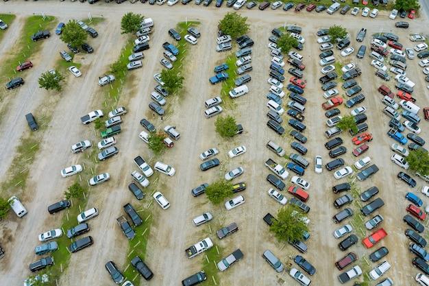 Vista aérea superior do leilão de automóveis, muitos lotes de carros usados estacionados distribuídos em um estacionamento.