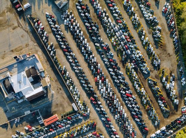Vista aérea superior do leilão de automóveis muitos lotes de carros usados estacionados distribuídos em um estacionamento.