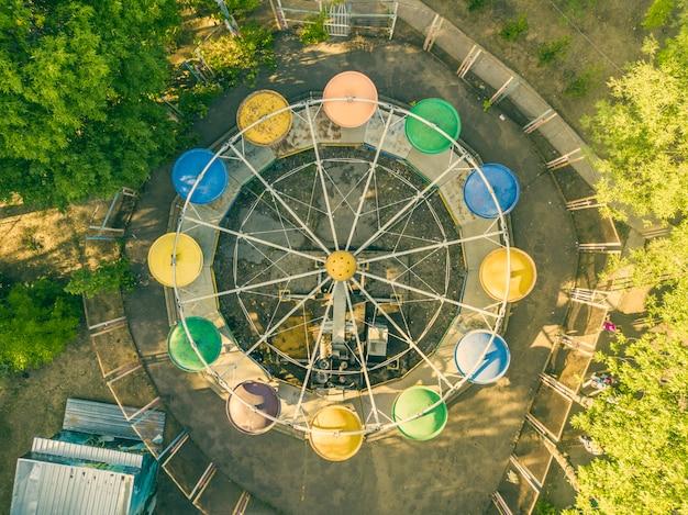 Vista aérea superior do parque da cidade caorusel com crianças felizes nas férias de verão.