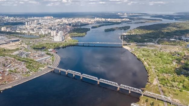 Vista aérea superior do rio dnieper nas ilhas kiev, trukhaniv e rybalskiy de cima, pontes e paisagem urbana da cidade de kiev, ucrânia