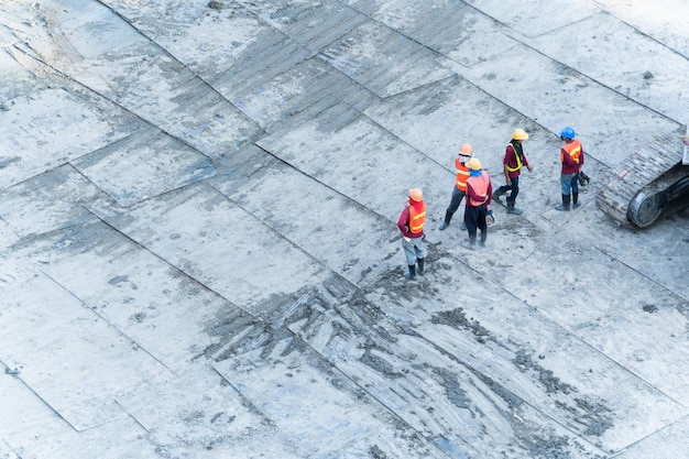 Vista aérea superior dos trabalhadores da construção civil trabalham na área de construção do projeto.