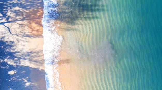 Vista aérea superior, praia com sombra água azul esmeralda e espuma de onda no mar tropical