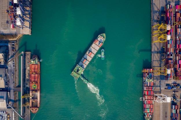 Vista aérea superior rebocador empurrando navio de contêineres para o cais para carga e descarga de contêiner por meio de guindaste para logística