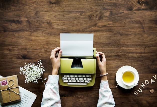 Vista aérea, um, mulher, usando, um, retro, máquina de escrever, passatempo, e, domingo, lazer, conceito
