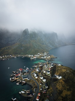 Vista aérea vertical da bela cidade de lofoten, na noruega, capturada no meio do nevoeiro