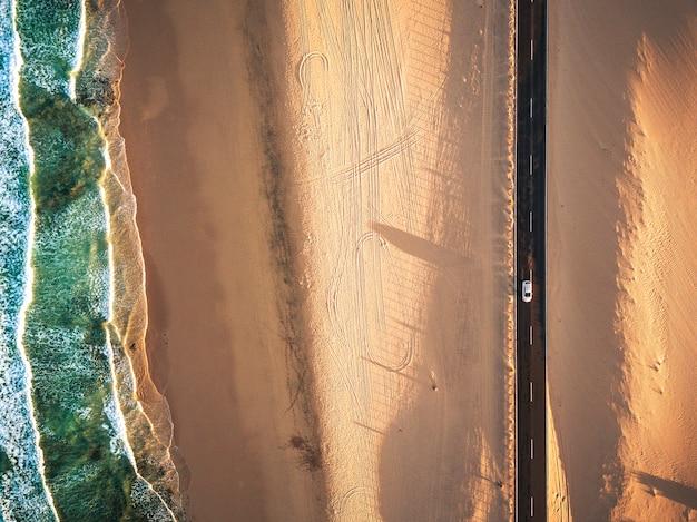 Vista aérea vertical da praia de areia tropical amarela com estrada longa preta e carro viajando - ondas do oceano azul e costa - hora do pôr do sol com sombra longa e bonita - conceito de férias de verão