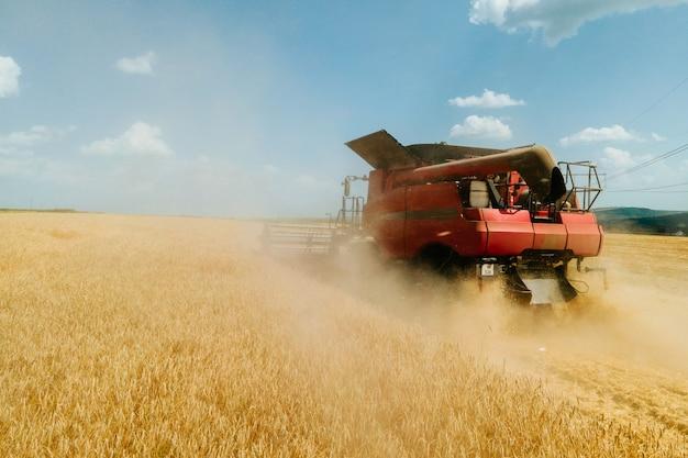 Vista aérea vista frontal da colheitadeira, colheita de trigo emite nuvens de poeira e fumaça conceito ...