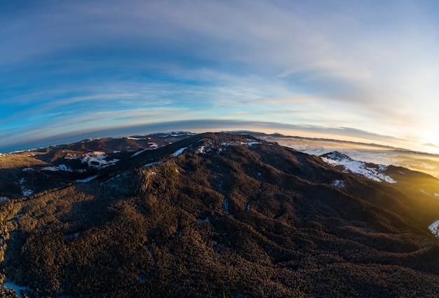 Vista aérea vista incrível das montanhas e encostas cobertas por densos bosques de abetos e neve em um dia ensolarado e gelado