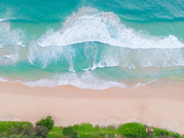 Vista aérea vista superior bela praia atual com coqueiros de areia branca e mar. vista superior da praia vazia e limpa. ondas quebrando na praia vazia de cima.