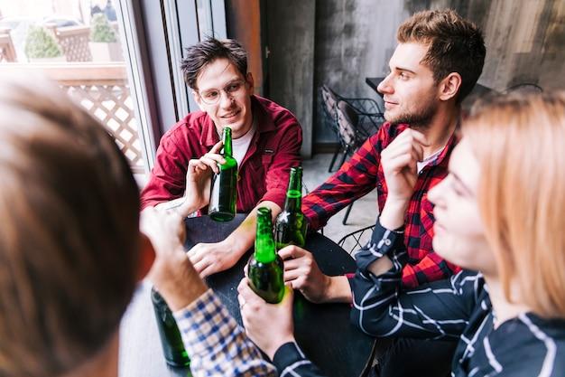 Vista alta ângulo, de, amigos, sentando, junto, desfrutando, a, cerveja