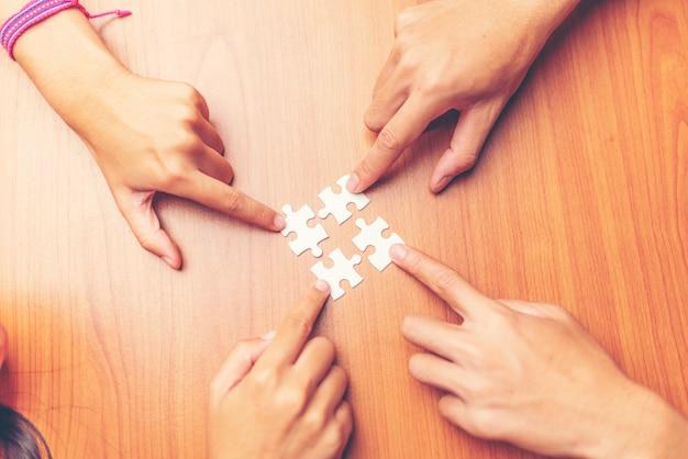 Vista alta ângulo, de, businesspeople, mão resolva quebra-cabeça, ligado, madeira, escrivaninha