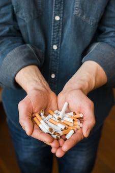 Vista alta ângulo, de, cigarros quebrados, em, mão homem