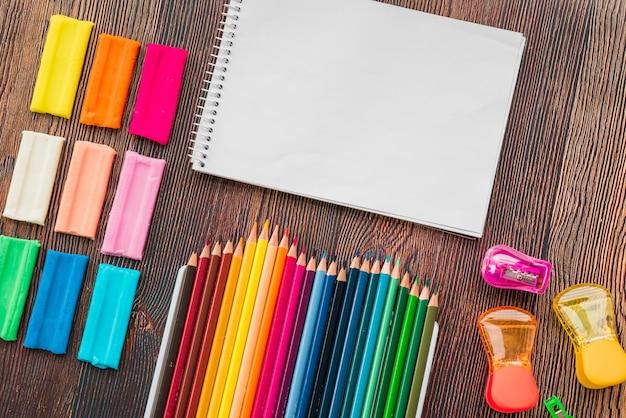 Vista alta ângulo, de, colorido, argila, e, lápis, com, branca, espiral, notepad