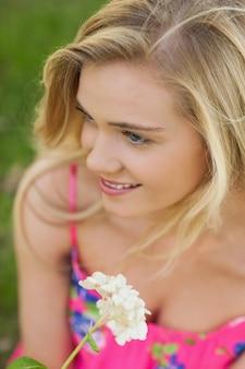 Vista alta ângulo, de, conteúdo jovem mulher, segurando, um, flor branca